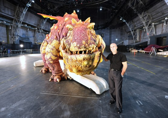 Jeffrey Katzenberg of Dreamworks poses with the large Gronckle animatronic dragon from the How to Train Your Dragon Arena Spectacular