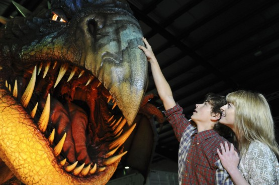 Rarmian Newton (Hiccup) and Sarah McCreanor (Astrid) pose with the large Deadly Nadder dragon from the How to Train Your Dragon Arena Spectacular